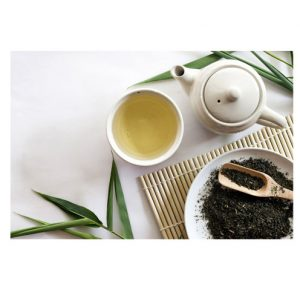 Photo of a teapot, a cup of herbal tea and some herbs